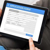 Sample application form on tablet computer, man using tablet
